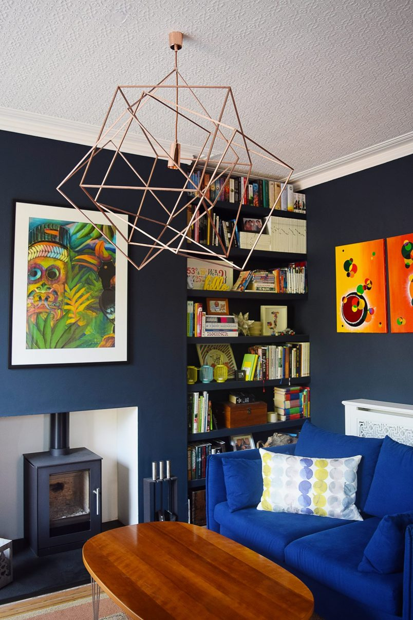 Cosy Lounge With Dark Walls, Wood Burner, Floating Shelves and Colourful Art | Little House On The Corner
