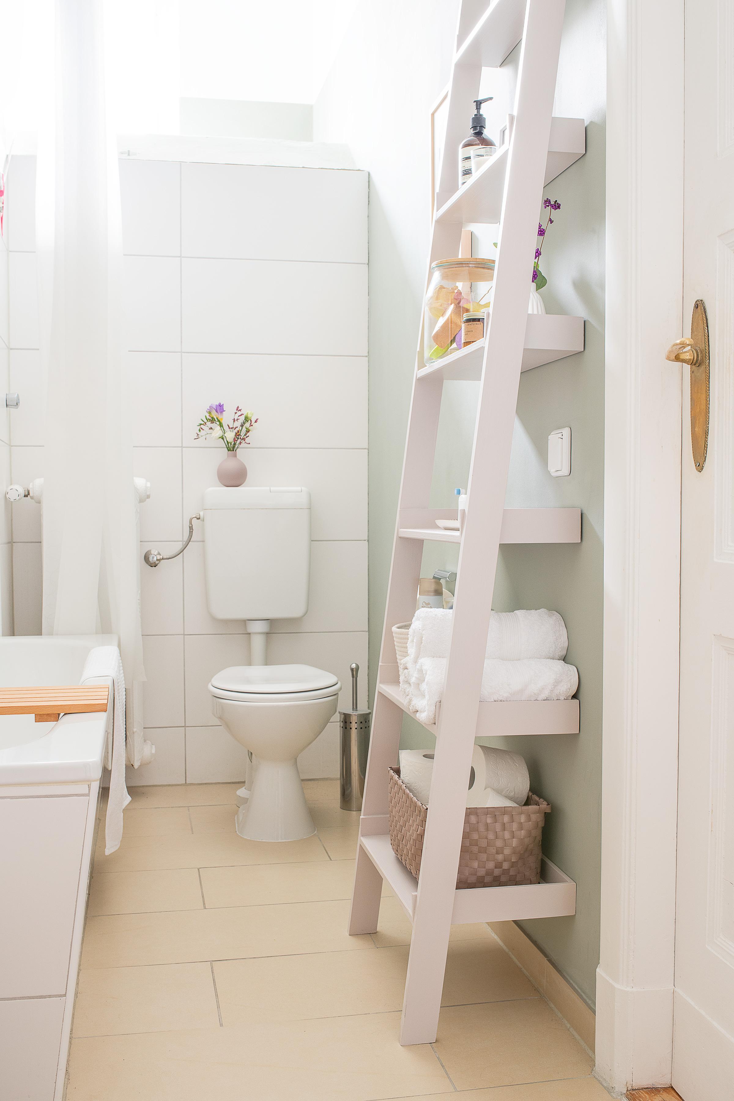 A cute pink DIY storage shelf ladder in a bathroom