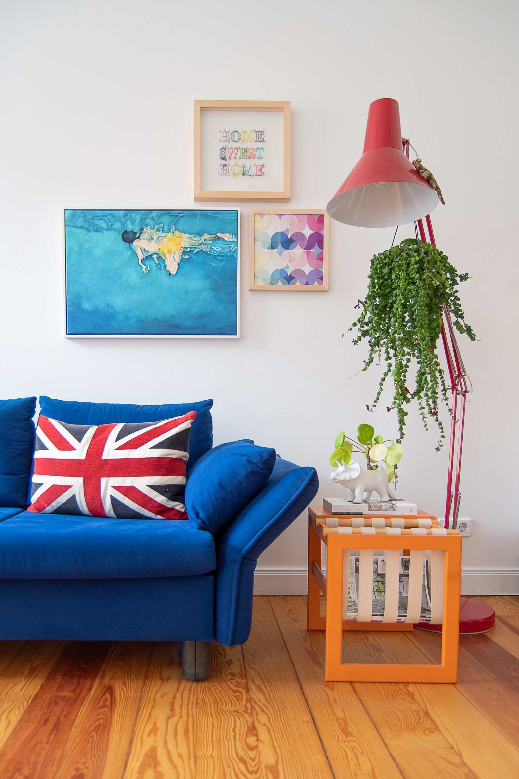 Dark blue sofa with orange magazine table and gallery wall | Little House On The Corner