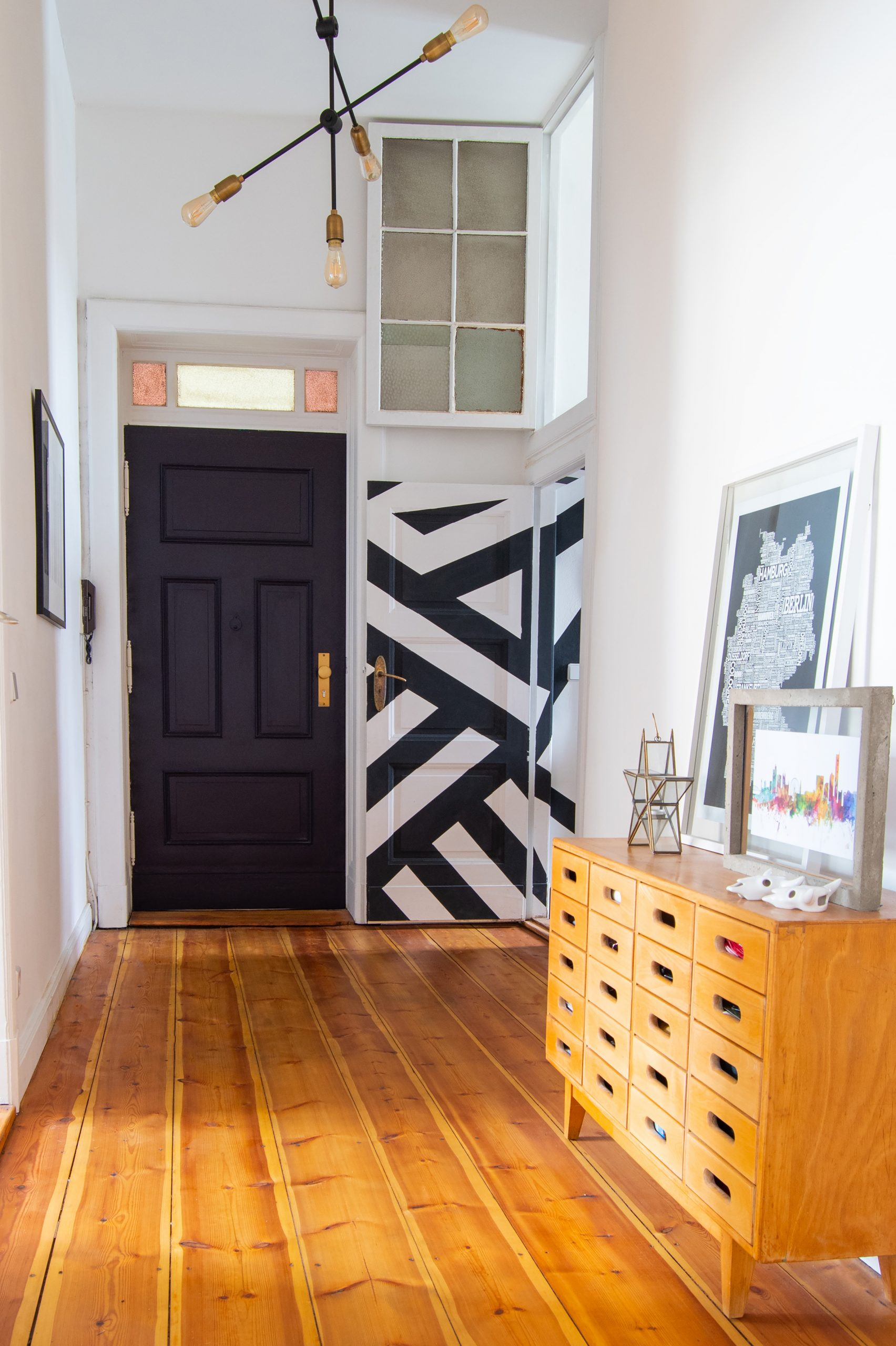 Hallway with sanded floorboards and paean black front door | Little House On The Corner