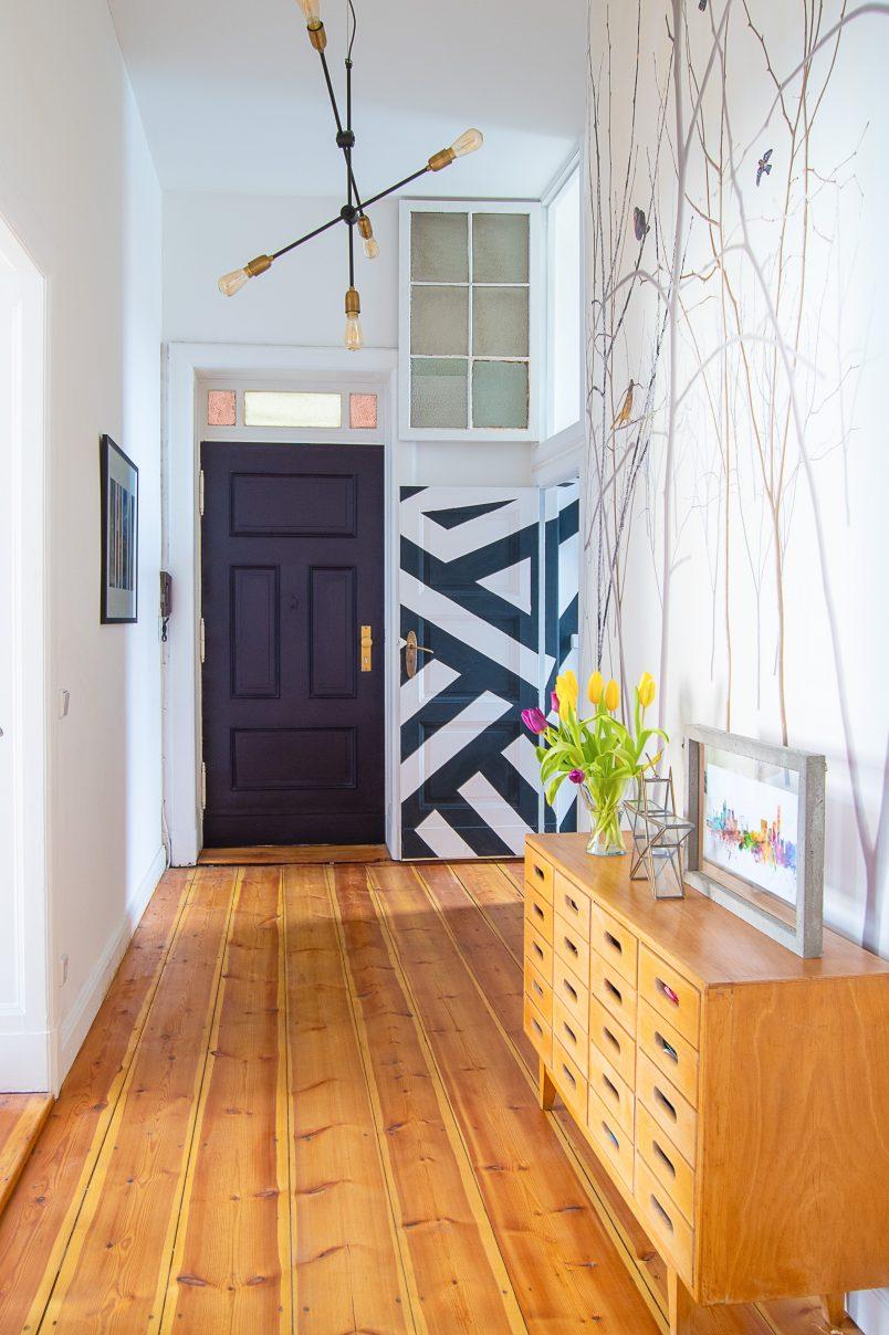 hallway with sanded floorboards and paean black front door