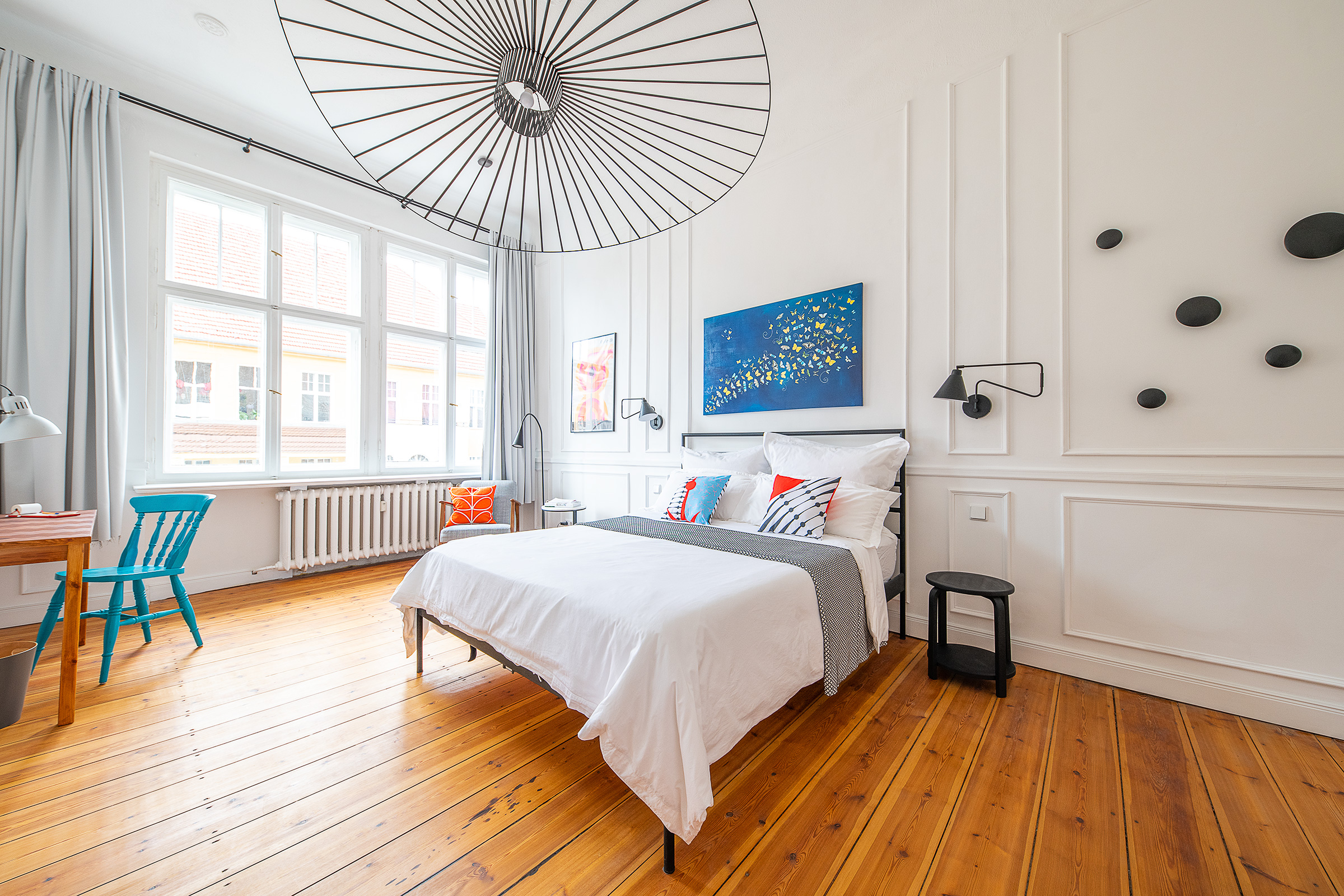 Bedroom with white panelled walls and sanded floorboards