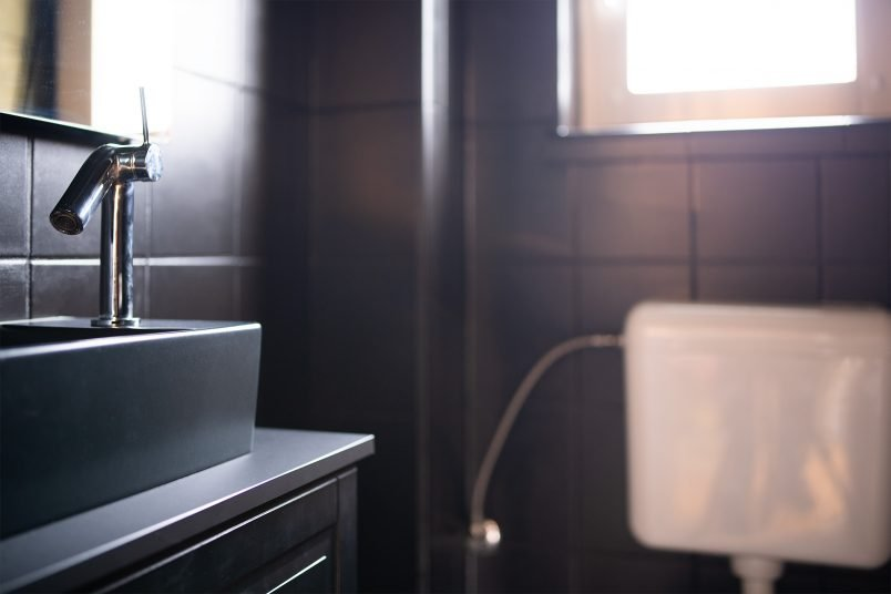All Black Guest Bathroom with black tiles and black washbasin