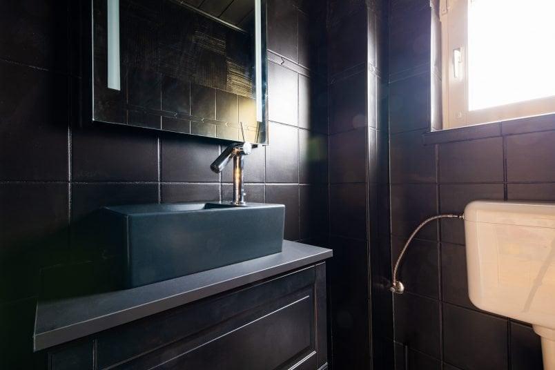 Black Vanity unit with black tiles and black washbasin
