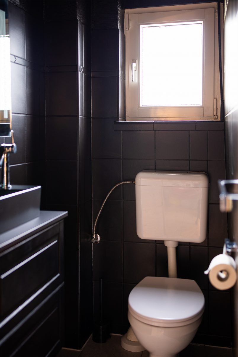 Black tiles, black washbasin and black cupboard