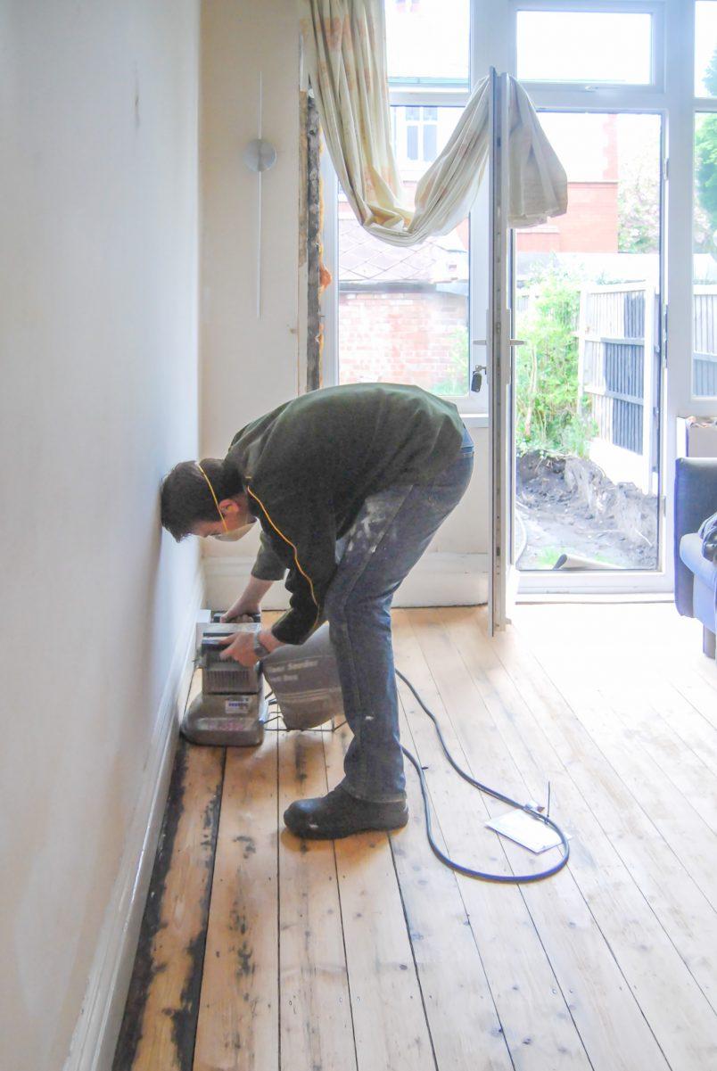 Sanding the edge of floorboards